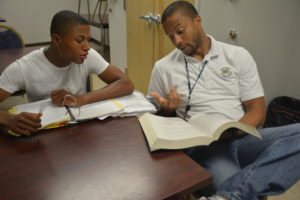PEO C3T Contractor Rick Burton (right) explains a math problem to Freestate ChalleNGe Academy Cadet Kevin Dingle during a tutoring session on APG South (Edgewood).   U.S. Army photo by Rachel Ponder, APG News